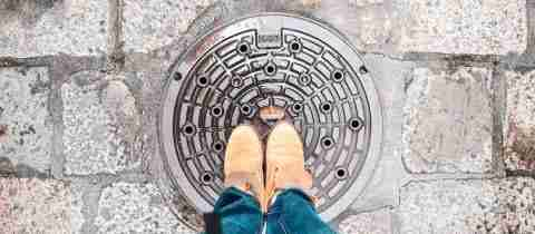 Image of a person standing with a manhole under their feet